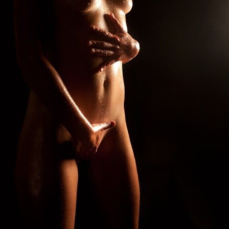 Wet body of a beautiful naked woman caressing herself in front of black background  photo