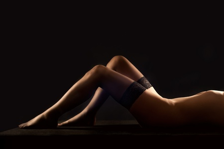 woman nude sexy: Beautiful long legs of a nude woman in erotic black stockings lying in front of black background