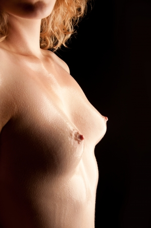 Closeup of beautiful wet breasts of a young woman in front of black background Stock Photo - 11386137