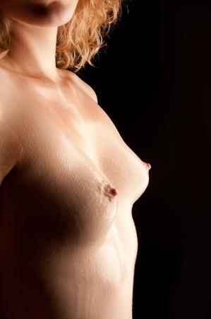 beaux seins: Gros plan d'beaux seins mouillés d'une jeune femme en face de fond noir Banque d'images
