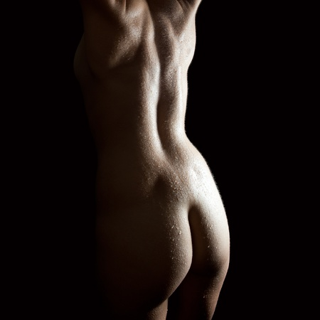 nude back: Beautiful back of a nude woman with wet body, closeup in front of black background  Stock Photo