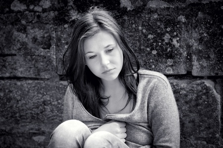 maltreatment: Outdoor portrait of a sad teenage girl looking thoughtful about troubles, monochrome photo Stock Photo