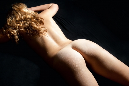 Beautiful back of a nude young woman with long blond curly hair and wet body lying in front of black background photo