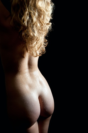 nude back: Beautiful back of a nude young woman with long blond curly hair and wet body lying in front of black background