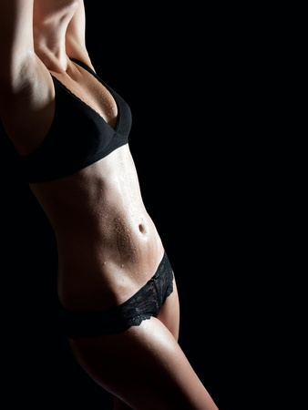 nude wet: Wet body of a beautiful young blond woman in black underwear, studio shot in front of black background