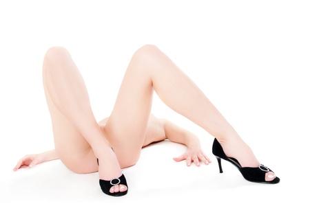junge nackte mädchen: Beine einer schönen nackten Frau in schwarzen High Heels, Nahaufnahme vor weißem Hintergrund