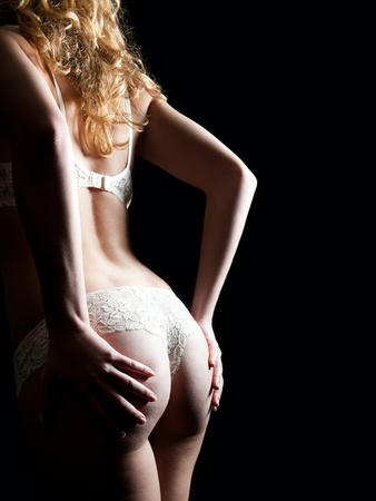 nude woman standing: Beautiful back and buttocks of a woman in whites panties and bra in front of black background  Stock Photo