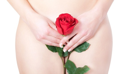Closeup of  a beautiful nude woman hiding her pubic region with a red rose, erotic concept, isolated front of white background