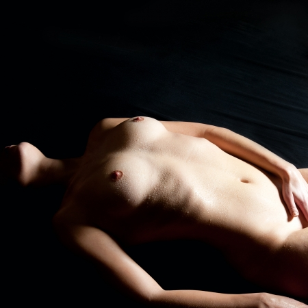 small breast: Beautiful nude woman lying on black bed loving herself, in front of black background
