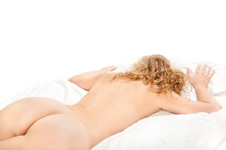 Beautiful nude woman lying on white bed in front of white background