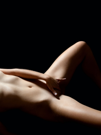 Beautiful nude woman lying on black bed loving herself, in front of black background