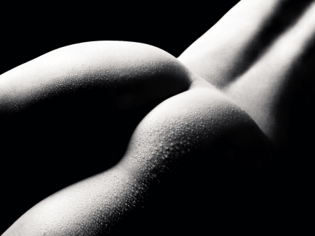 Beautiful buttocks of a nude young woman with wet body, closeup in front of black background, black and white photo  Stock Photo
