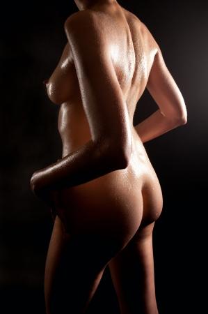 mujer negra desnuda: Hermosa vista trasera de una joven desnuda en frente de fondo negro Foto de archivo
