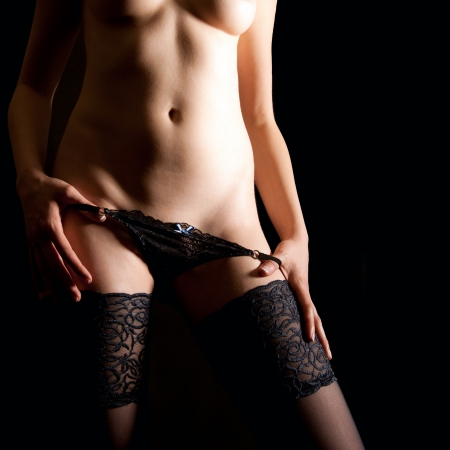 Beautiful young woman undressing black panties in front of black background Stock Photo - 12941026