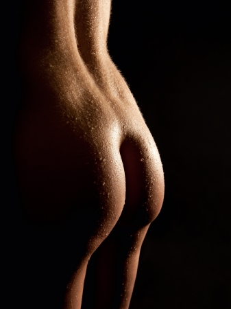 Beautiful buttocks of a nude young woman with wet body, closeup in front of black background Stock Photo - 12898130