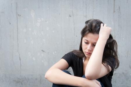 Odkryty portret smutnym nastolatka szuka mi o kłopotach przed szarą ścianą