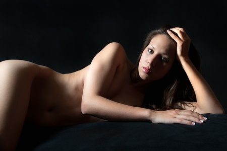 Classical nude of a beautiful young woman lying on black bed in front of black background Stock Photo