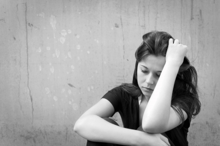 pullovers: Outdoor portrait of a sad teenage girl looking thoughtful about troubles, monochrome photo Stock Photo