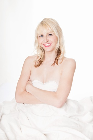 mujer desnuda sentada: Hermosa mujer rubia desnuda esconde detr�s de la ropa de cama blanca delante de fondo blanco