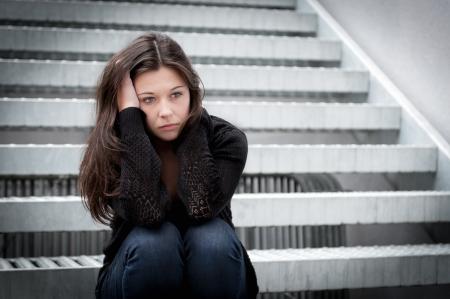Outdoor portret van een droevig tienermeisje op zoek nadenkende over de problemen in de voorkant van een grijze muur