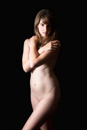 Beautiful nude brunette woman covering hear breasts, beauty concept