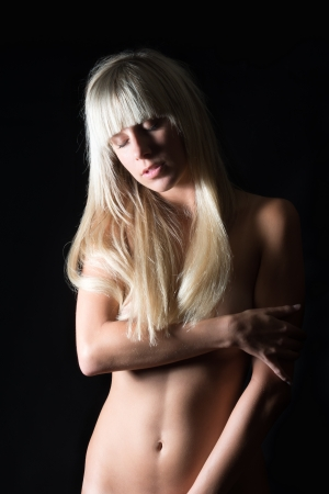 Erotic nude woman covering her nude body with her arms and hands, in front of black background Stock Photo - 14843578
