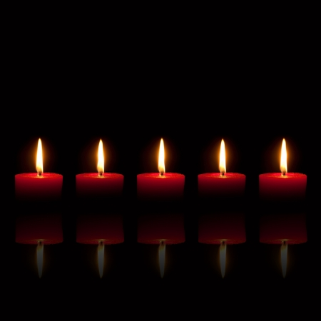 five objects: Five red candles burning in front of black background, with reflection of flames Stock Photo
