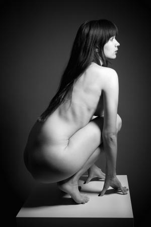 desnudo artistico: Desnudo art�stico cl�sico de una mujer delgada hermosa con el pelo largo delante de fondo oscuro
