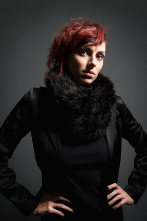 erotically: Portrait of a beautiful young woman with read hair wearing black blazer and fur in front of dark background Stock Photo