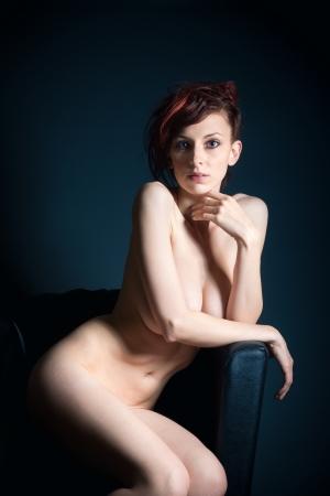 mujer desnuda sentada: Forme el retrato de una mujer desnuda hermosa y elegante que se sienta en sill�n negro delante de un fondo oscuro
