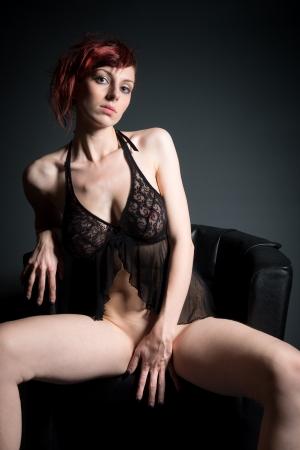 mujer desnuda sentada: Forme el retrato de una hermosa mujer desnuda sentada en sill�n negro delante de fondo oscuro