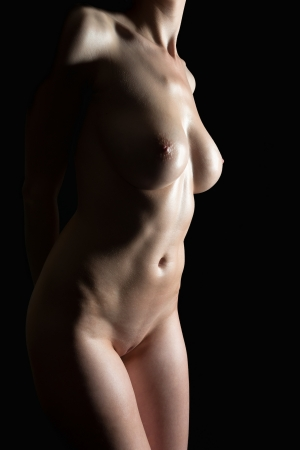 Beautiful torso of a sexy nude woman with oiled body in front of black background
