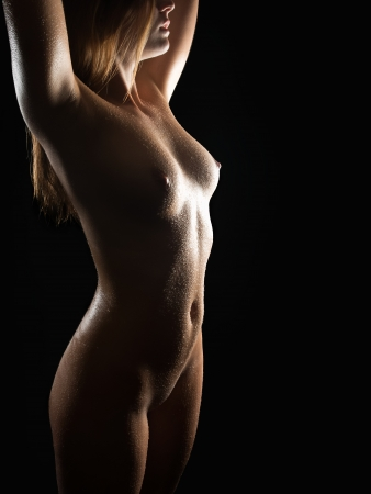 Classical nude of an erotic blond woman with wet body in front of black background