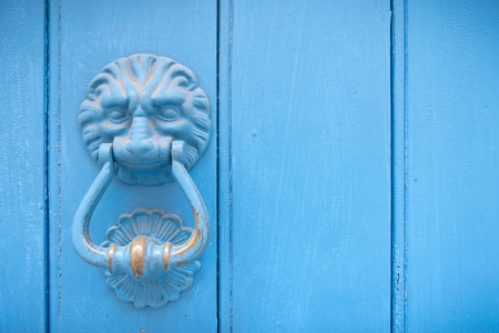 Lion head door knocker on an old blue wooden door in France photo