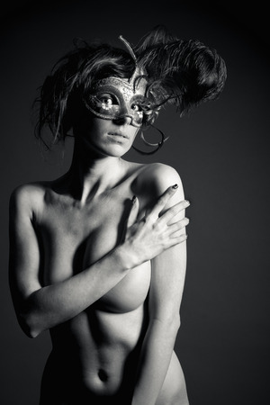 An attractive nude woman wearing a mysterious venetian mask in front of black studio background, monochrome  photo