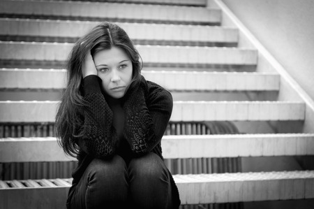 Outdoor portrait of a sad young woman looking thoughtful about troubles, sitting on metal stair, monochrome photo