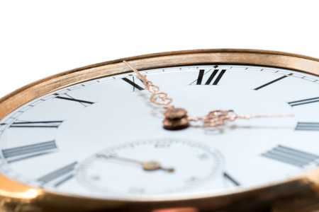 Extreme closeup of an antique golden pocket watch isolated on white background. Concept of time, past or deadline photo