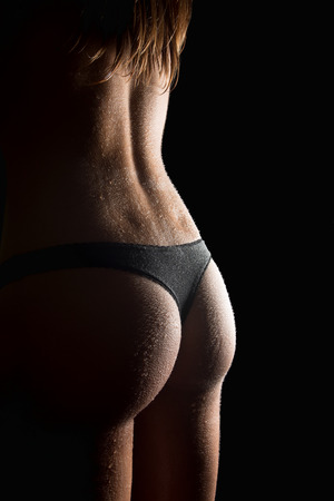 Closeup of a beautiful wet female bottom in black panties in  front of black background photo