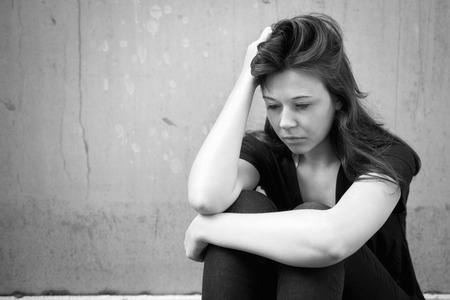 Outdoor portrait of a sad young woman looking thoughtful about troubles in front of a gray wall, monochrome photo