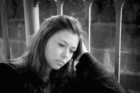 mujeres tristes: Retrato al aire libre de una joven mujer triste mirando pensativo sobre apuros, monocromo