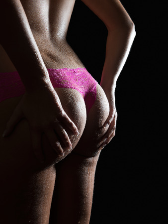 Closeup of an attractive wet female bottom in pink panties in front of black studio background photo