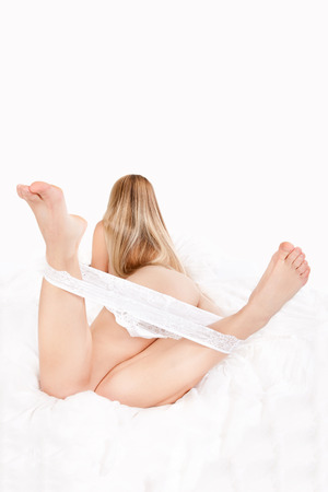 Attractive woman with undressed white panties lying on white bed with her feet up in the air  photo