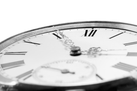 Extreme closeup of an antique golden pocket watch isolated on white background, monochrome. Concept of time, past or deadline photo