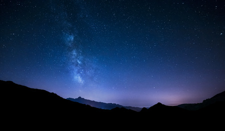 stars: night sky panorama with moving stars and Milky way behind mountain Stock Photo