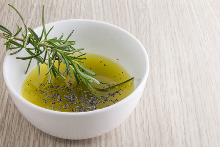 extra virgin olive oil: rosemary olive oil sauce in bowl on wood background