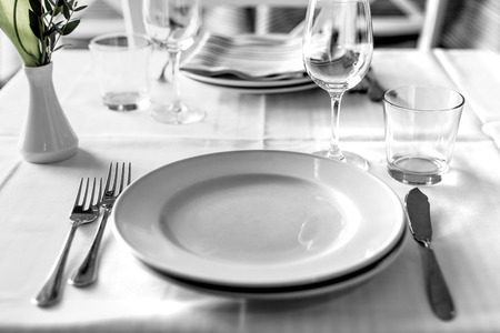 empty plate: table setting in restaurant interior, desaturated