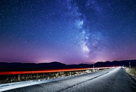 cielo nocturno con la Vía Láctea y las estrellas. Camino de la noche iluminada por coche. La luz se arrastra Foto de archivo