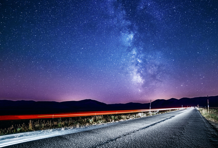 Night sky with milky way and stars. Night road illuminated by car. Light trails Фото со стока