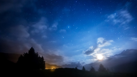 night sky stars and moon across mountain Stock Photo