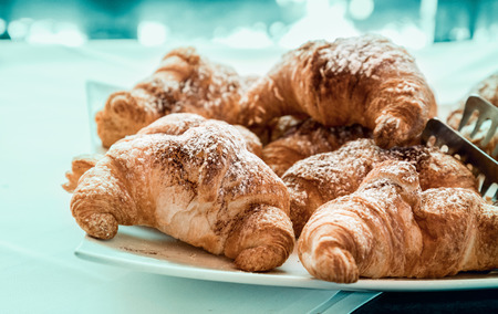 pastries: Croissant fresh bakery pastry over light blue background. Filtered image